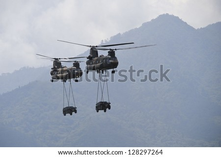 Two Chinook helicopters transporting Cars - stock photo