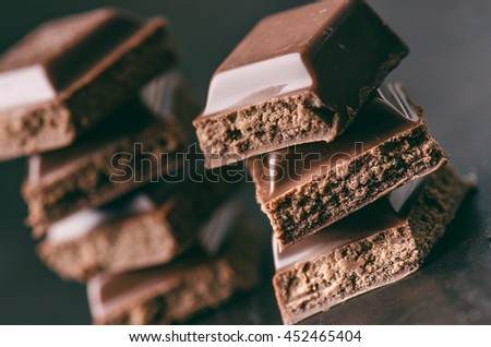 Two chocolate buildings on a dark background. energy and sugar. Broken bar. Chocolate blocks stack  - stock photo