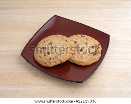 Two chocolate chip gluten-free cookies on a deep red plate atop a wood table top. - stock photo