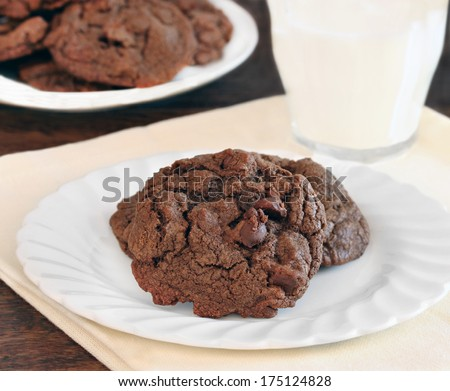 Two chocolate, chocolate chip cookies on a plate with a serving of milk. - stock photo