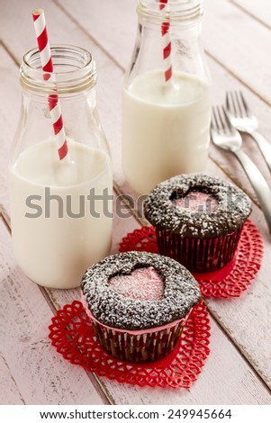 Two chocolate cupcakes with heart shaped cutouts filled with pink frosting sitting on red lace doilies and two bottles of milk with straws