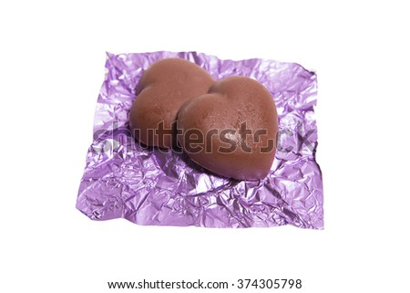 Two chocolate heart candy in purple foil on white background - stock photo
