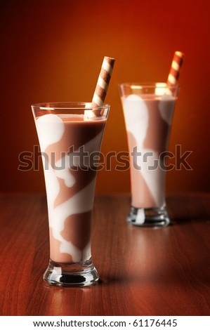 Two chocolate smoothie drinks in tall glass both with spiral wafer straws - stock photo