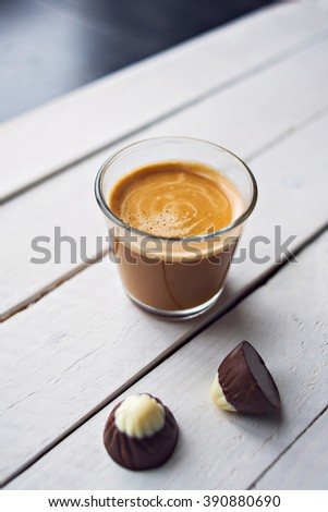 Two chocolates candies and cup of espresso on the white wooden table. Top view. Place for text.