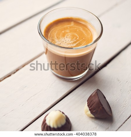 Two chocolates candies and cup of espresso on the white wooden table. Top view. Place for text. - stock photo