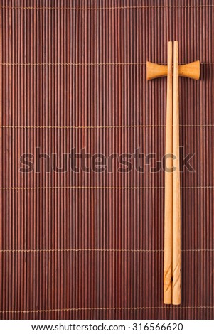Two chopsticks on a bamboo mat - stock photo