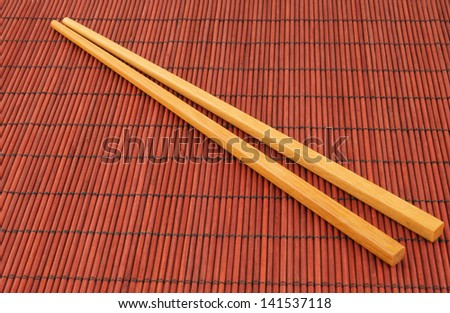 Two chopsticks on red bamboo background - stock photo