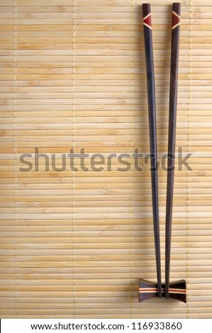 Two chopsticks on sushi mat - stock photo