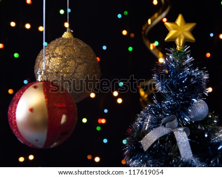 two Christmas ball hanging on a black background with bright lights and decorated the Christmas tree - stock photo