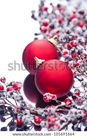 Two Christmas baubles and holly berries on a silver reflective surface - stock photo