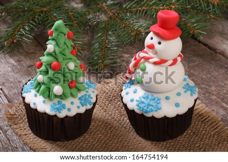 Two Christmas cupcake: Christmas tree and snowman on the table - stock photo