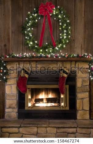 Two Christmas stockings hanging by the fireplace. - stock photo