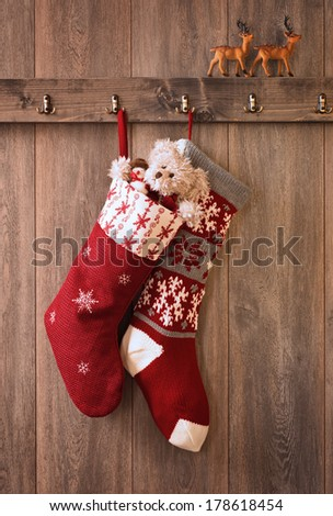 Two Christmas stockings with teddy bear and snowman gifts - stock photo