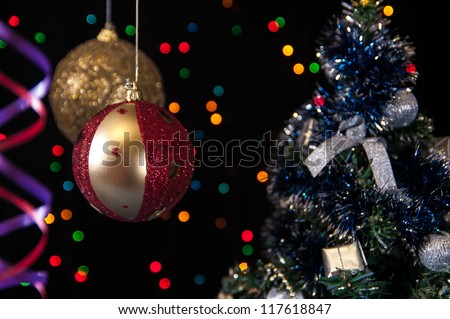 two Christmas tree ball,the serpentine,a decorated Christmas tree on a black background with lights