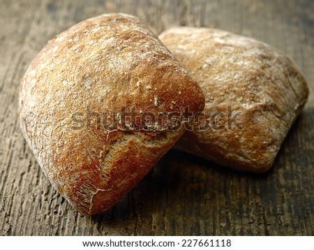 two ciabatta bread buns on wooden table - stock photo