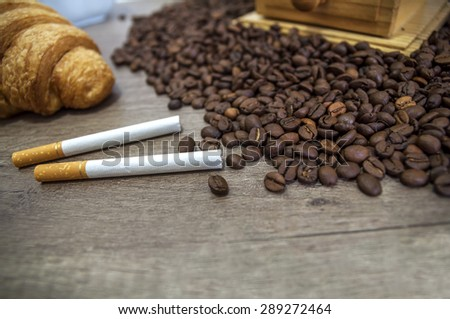 Two cigar, croissant and coffee beans on kitchen table - stock photo