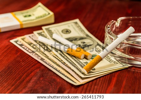 Two cigarettes are on the dollars, lies next to a pack of bills and other cigarette on the glass ashtray. Focus on the cigarette in the ashtray