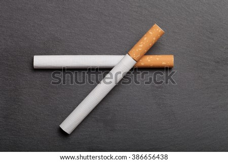 Two cigarettes on a black slate cutting board. - stock photo