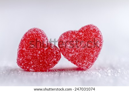 Two cinnamon heart candies coated with sugar sitting on white background - stock photo