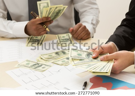 Two clark count earned money. - stock photo