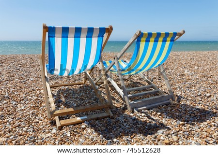 Two Classic Deckchairs On The Pebble Beach Waiting For Someone To Sit
