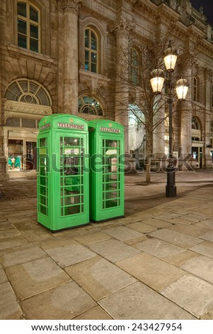 two classic english phone boxes near bank station painted green at night - stock photo