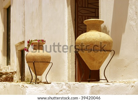 Two clay amphorae against light colored stone wall - stock photo