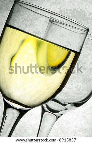 Two clear glasses with yellow drink on grey background - stock photo