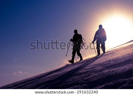 Two climbers are moving to the top of the glacier - stock photo
