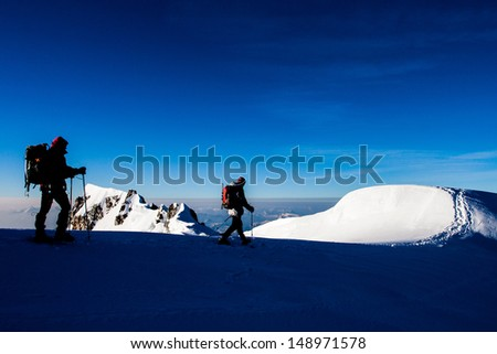 Two climbers on a snow ridge in the Alps - stock photo