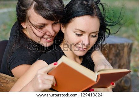 Two close woman friends enjoying reading a book together as they sit on a wooden bench outdoors with the breeze blowing their hair