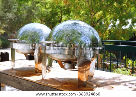 two closed stainless steel cloche on wooden table on restaurant outside party - stock photo