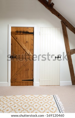 Two closed wooden doors in a loft room.  One is painted white, the other is unpainted. - stock photo