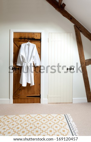 Two closed wooden doors in a loft room.  One is painted white, the other is unpainted and has a bathrobe hanging on a hook.