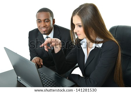 Two co-workers looking at laptop working together - stock photo