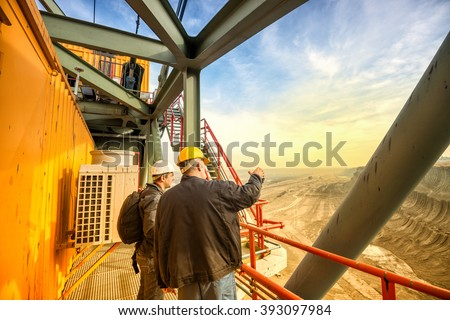 Two coal mine engineers with protective helmets standing and talking on a huge drill machine, talking and watching at the digging site. Beautiful and colorful sky in the background. Rear view. - stock photo