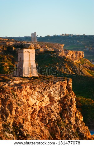 Two Coastal defense towers awash in the golden light of sunset, silent sentinels of the past, forming part of the defensive perimeter built by the Knights of St John during their 200 year stay - stock photo