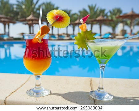 Two cocktail drinks by a tropical resort swimming pool - stock photo
