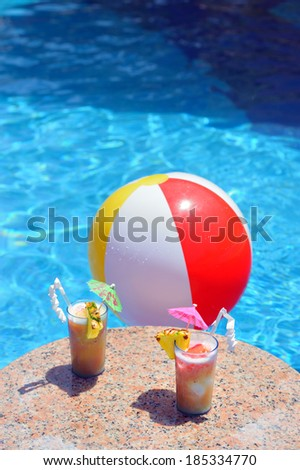 Two cocktail glasses and a water ball by a blue water of swimming pool (you text on top of the image) - stock photo