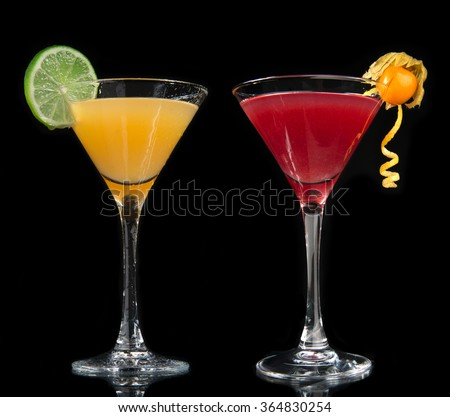 Two cocktails cosmopolitan cocktails decorated with citrus lemon twist yellow and red martini drink with strawberry isolated on a black background