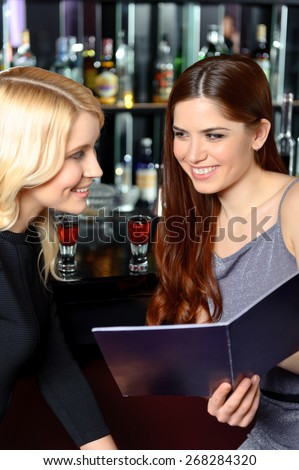 Two cocktails for the start. Close-up of two cheerful women holding a menu and smiling to each other at the bar counter