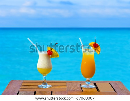 Two cocktails on table, sea background