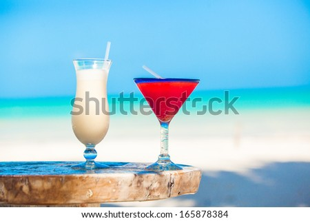 Two cocktails: pina colada and strawberry margarita on wooden table - stock photo