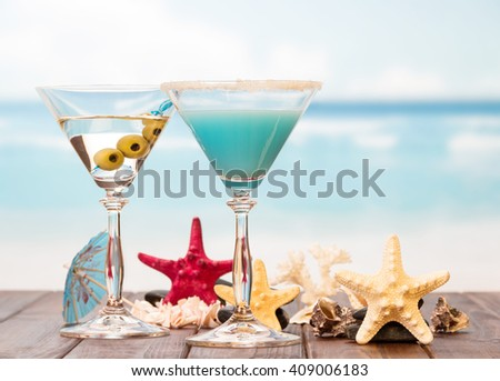 Two cocktails, starfish and sinks on sea background.