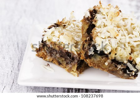 Two coconut chocolate chip bars over a rustic background. Shallow depth of field. - stock photo