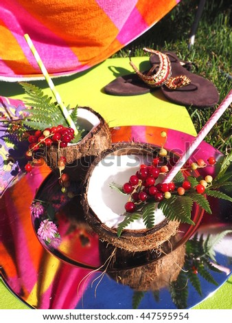 Two coconut shells containing some summer cocktail in colorful bohemian setting.