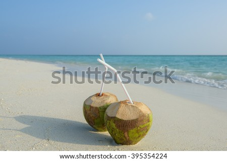 Two coconuts with straw on a untouched maldives beach