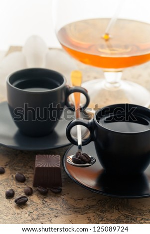 two coffee cups and coffee beans sprinkled with dessert and a glass of wine - stock photo