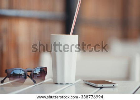 two coffee cups at the restaurant or cafe on table with smartphone and sunglasses.Fresh coffee with milk in cup with cookie close up. Selective focus. - stock photo