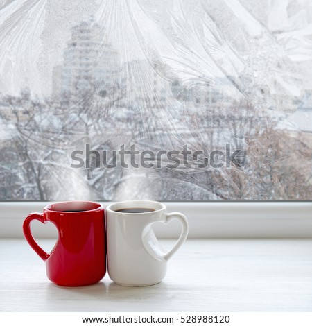 Two coffee cups on a windowsill. The view from the window on city streets